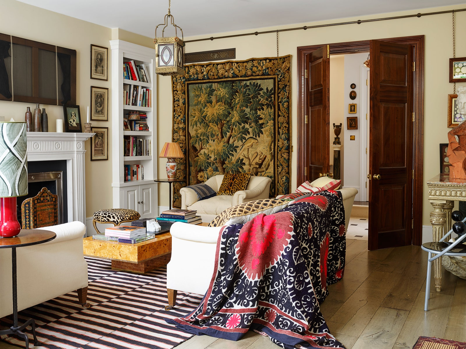 An antique suzani from Robert Kime is draped over a custom sofa in the morning room. Jamb fireplace surround antique...